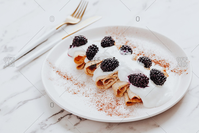 Delicious crepes with yoghurt and blackberries served on plate with cinnamon near silverware on marble table