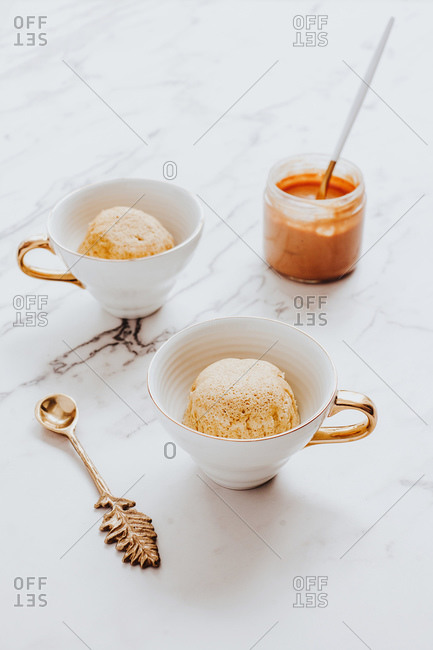 Cups with ice cream bowls placed near ornamental spoon and jar of peanut butter on marble table