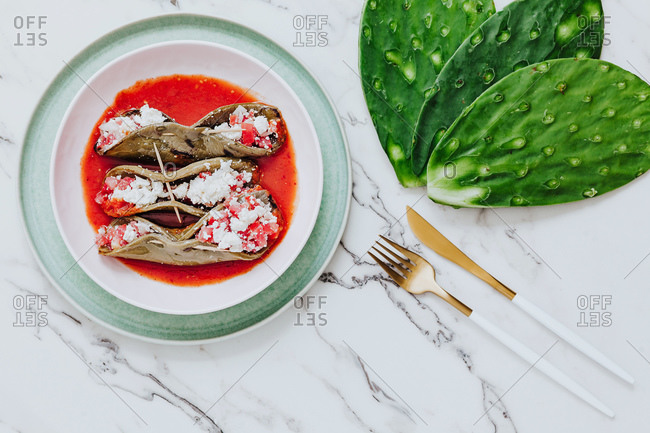 From above appetizing roasted cactus leaves with tasty mix in tomato sauce on plate in composition with golden cutlery and fresh ingredient on white table in light modern kitchen