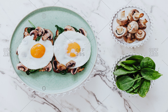 Top view of tasty fried eggs placed of yummy sandwiches with mushrooms and spinach on plate on marble table