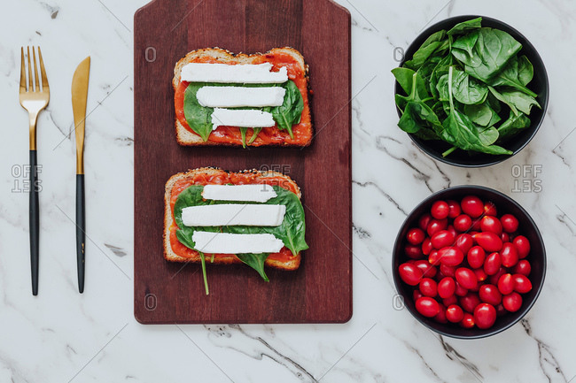 Top view of bread toasts with green spinach and mozzarella cheese on tomato sauce composed on wooden board with bowls of ingredients and cutlery on marble surface