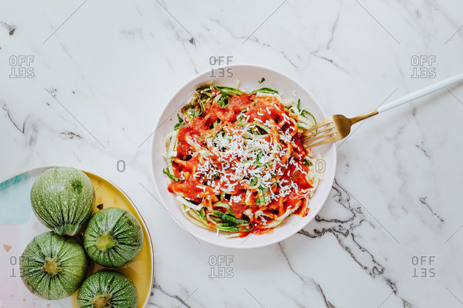 From above delicious healthy mix of fresh green pasta made of round zucchini with tomato sauce and topped with grated cheese place on marble surface with fork
