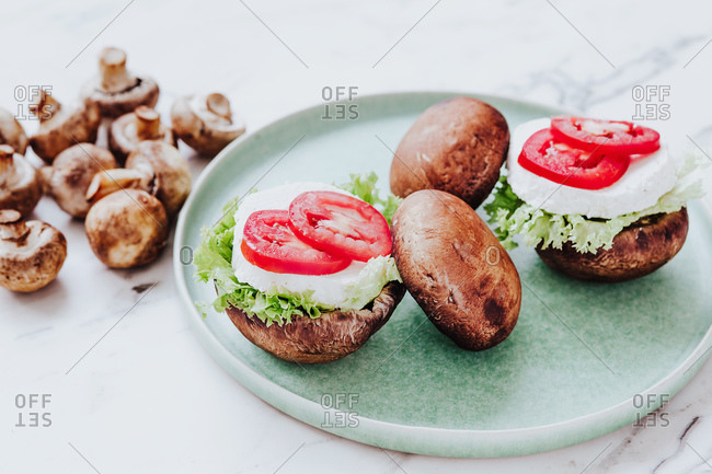 High angle of healthy bowls with mushroom mushrooms stuffed with lettuce and cheese with tomato slices served on green plate