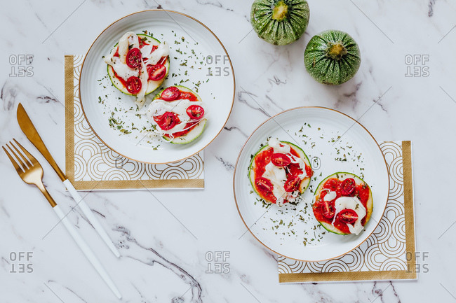 From above delicious healthy sandwiches with slices of fresh green zucchini with melted mozzarella and cherry tomatoes on white plates with golden cutlery