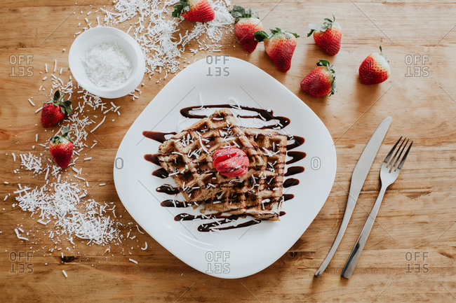 Soft sweet waffles and strawberries served on plate with yummy chocolate syrup and coconut flakes on wooden table near silverware