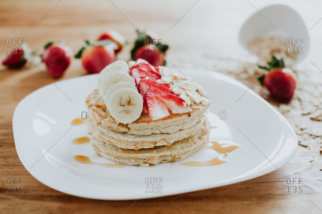 Closeup stack of yummy pancakes with pieces of banana and strawberry served on plate with almond flakes and honey during breakfast