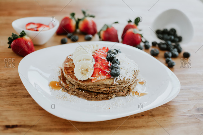 Stack of tasty pancakes served on plate with pieces of banana and strawberry and fresh blueberries with coconut flakes during breakfast