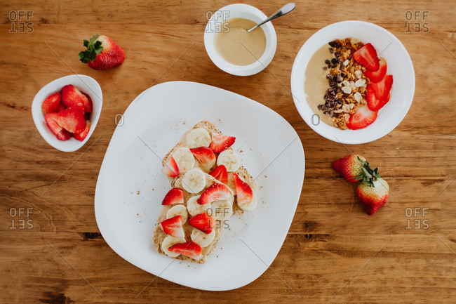 Delicious banana and strawberry sandwiches with sweet puree placed on plate during breakfast on wooden table