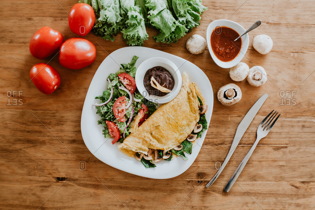 Top view of plate with vegetarian mushroom taco and healthy vegetable salad placed on wooden table near ripe tomatoes with lettuce and sauce