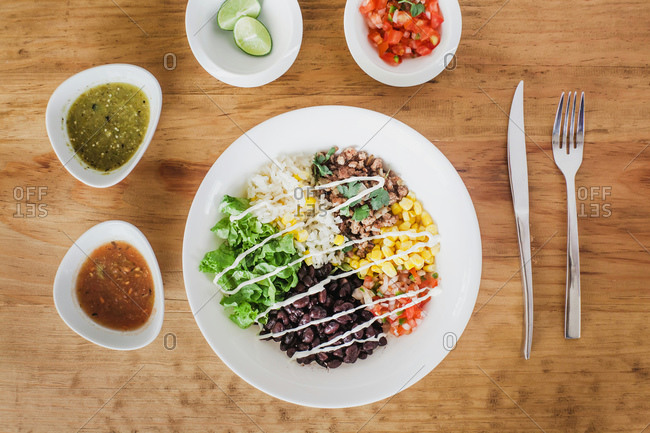 Top view of lettuce and beans with chopped tomatoes placed near corn kernels and grain in bowl on wooden table near various sauces with lime and silverware