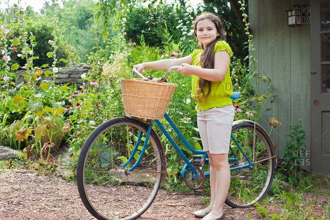 Portrait of girl with bicycle in garden