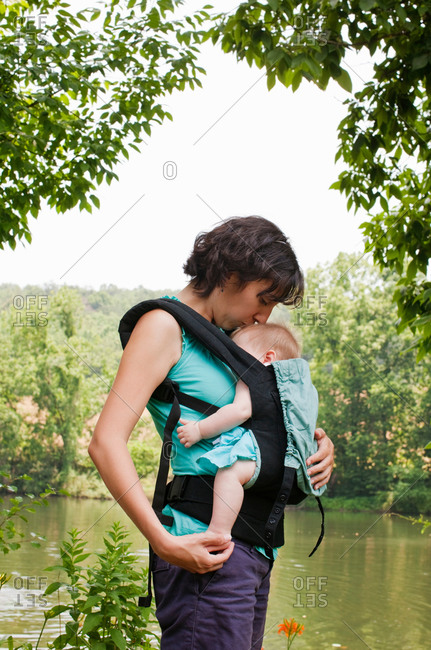 Mother kissing baby girl in carrier while going for walk