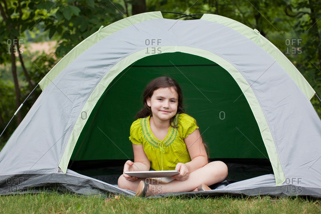 Girl studying on tablet in tent in backyard