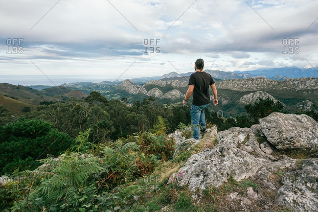 Back view of faceless male in casual outfit standing on edge of cliff and enjoying amazing scenery of mountain range against cloudy sky in Alicante in Spain