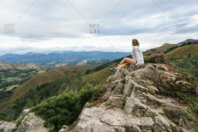 Side view of young faceless female in casual wear sitting on edge of cliff and admiring view of mountain green beautiful range while travelling on summer day in Asturias in Spain