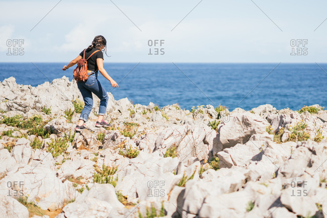 Unrecognizable woman walking on hill in nature