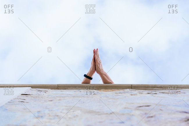 From below of unrecognizable crop person with black bracelet on hand clapping hands against blue cloudy sky on rooftop in city