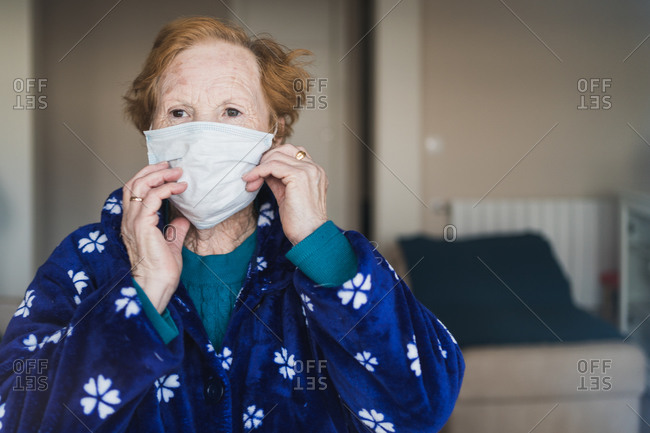 Senior female with red hair in blue robe and medical mask looking at camera while standing in hospital room
