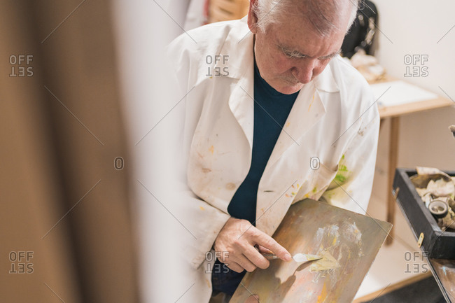Aged man painting picture with brush