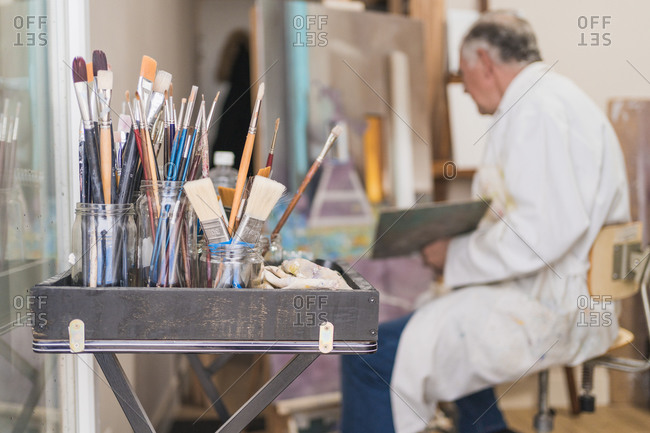 Many paintbrushes in glass on table