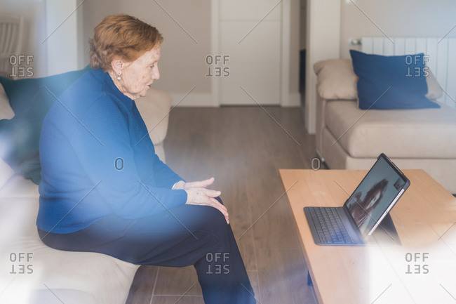 Old woman communicating with daughter on video chat on laptop