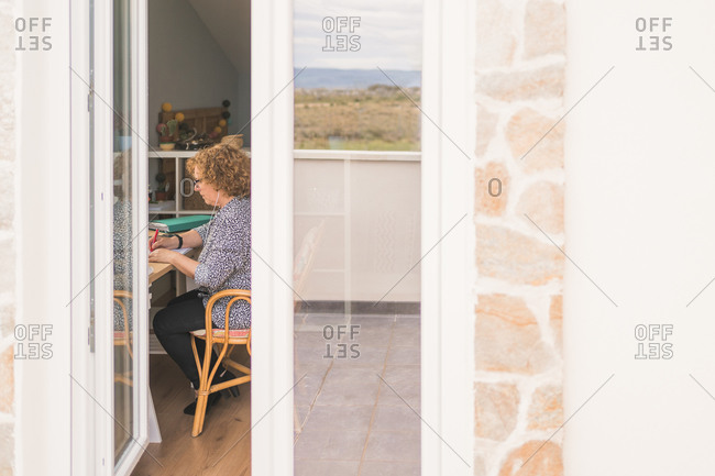 Through window side view of serious adult woman in casual clothes and eyeglasses taking notes with pen in notebook while working in cozy chair at table at home