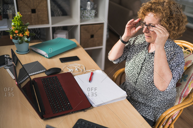 Side view of focused adult woman in casual clothes enjoying music in earphones with closed eyes while resting during work on laptop and notebook
