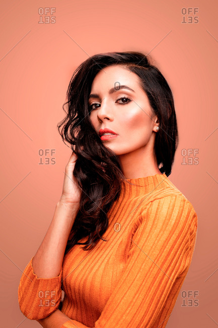 Charming confident young brunette female with long wavy hair and perfect makeup wearing casual orange sweater looking at camera while standing against pink background