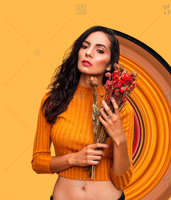 Confident young female model in trendy orange crop top holding bouquet of fresh flowers and looking at camera while standing against bright orange wall with geometric ornament in studio