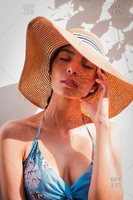 Tranquil young female in sundress and straw hat resting near white wall and enjoying sunny summer day during holidays