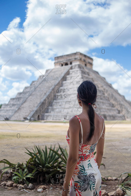 Anonymous female traveler enjoying view of ancient building on sunny day in Mexico