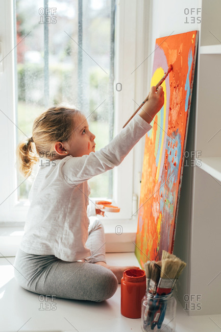 Creative blond girl in casual clothes sitting on window sill against window and painting with paintbrush large multi colored rainbow on orange canvas