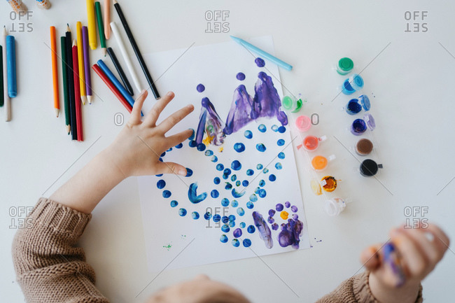 Cute child in casual outfit drawing paints with fingers while sitting at table with color pencils and scissors at light kindergarten