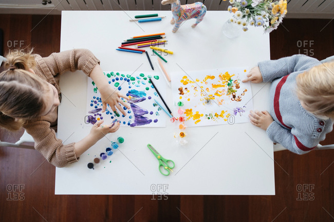 Preschool brother and sister painting together at home