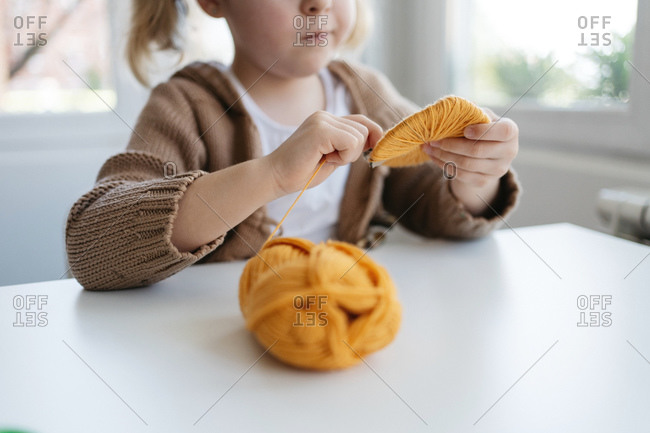 Little girl in casual wear winding woolen threads onto cardboard template to make handmade pompom for hat in cozy living room