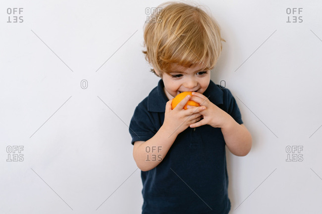 Funny blond little boy in casual clothes eating half of orange looking away with smile while standing against white background