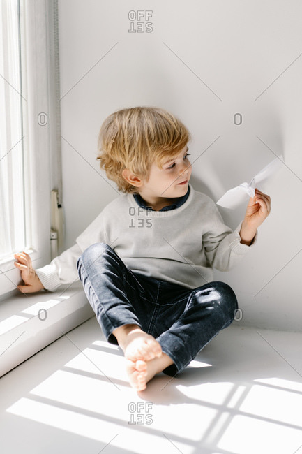 Happy blonde little child in casual clothes playing with paper airplane while sitting barefoot on window sill on sunny day