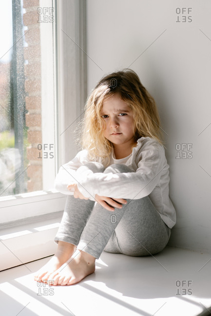 Annoyed little girl with curly hairs wearing gray cozy pajamas looking at the camera with dissatisfaction while sitting on sill with crossed arms