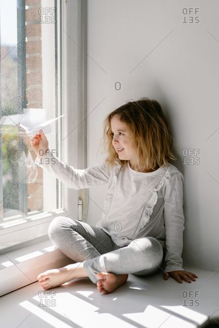 Happy blonde little girl in pajamas playing with paper airplane while sitting barefoot on window sill on sunny day