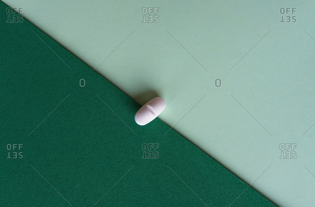Top view of prescription pill for flu treatment placed on green and turquoise sheets of paper