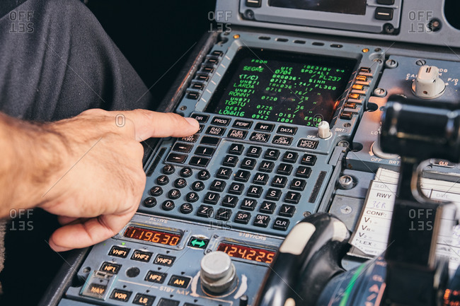 Crop anonymous male pilot using keyboard of flight management system in cockpit of modern aircraft during flight