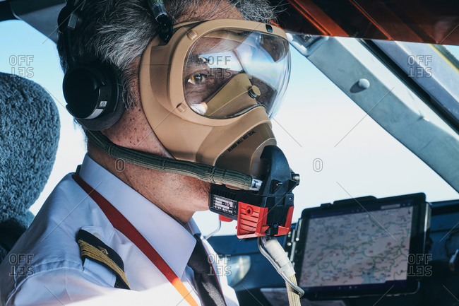 Pilot in mask operating airplane during flight