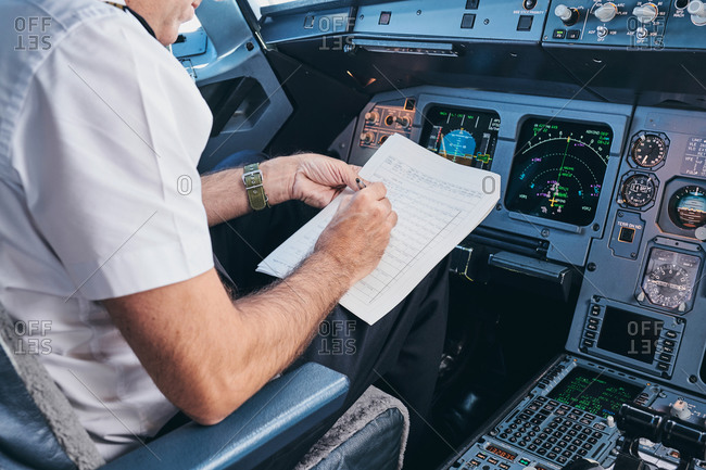 Side view of crop male aviator sitting in cockpit and filling in document while preparing for flight in modern aircraft