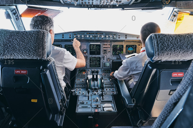 Back view of male pilot and co pilot using instrument panel in cockpit of modern passenger aircraft during flight