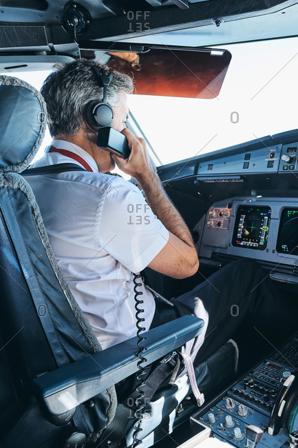 Side view of male captain communicating via VHF radio while sitting in cockpit of modern aircraft and preparing for flight