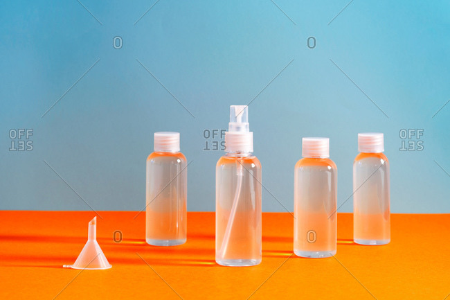 several clear bottles with hydrochloric gel along with a funnel to fill serves to disinfect covid-19's hands