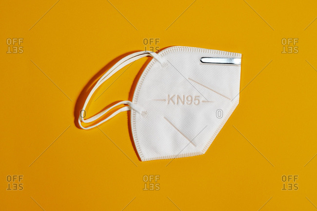 White mask with reusable KN95 protection index for virus protection on yellow background