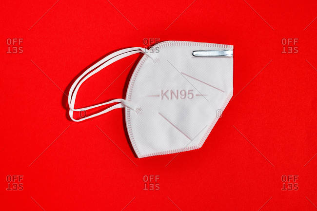 White mask with reusable KN95 protection index for virus protection on red background