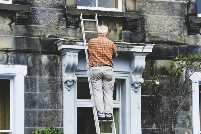 Senior anonymous man repairing door of old mansion