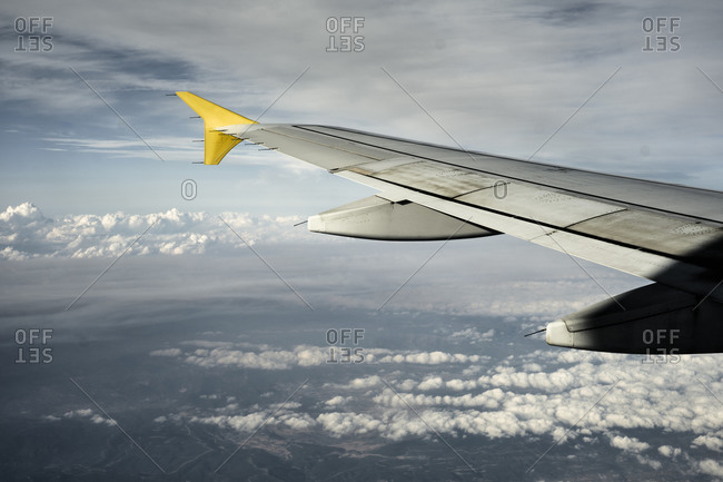 Wing of modern aircraft flying high above cloudy terrain with cloudy sky to sunny Ibiza